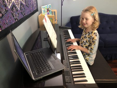 Child learning piano through Air House Music Academy's online lessons